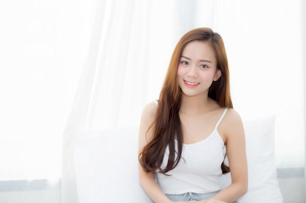 Schöne asiatische frau des portraits, die sitzt und lächeln das fenster