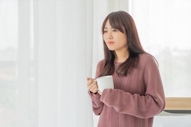 Schöne asiatische frau, die am morgen kaffee trinkt