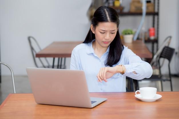 Schöne asiatische frau, die an laptop im café arbeitet