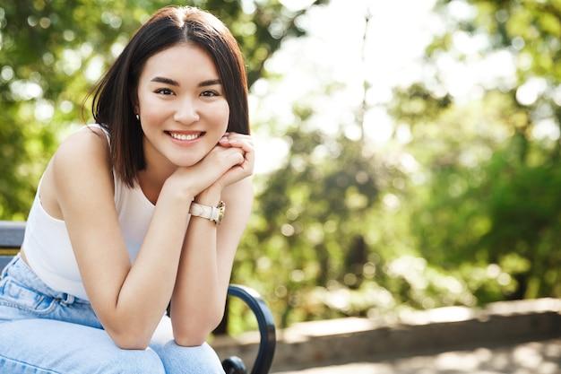 Schöne asiatische frau, die auf bank sitzt und lächelt