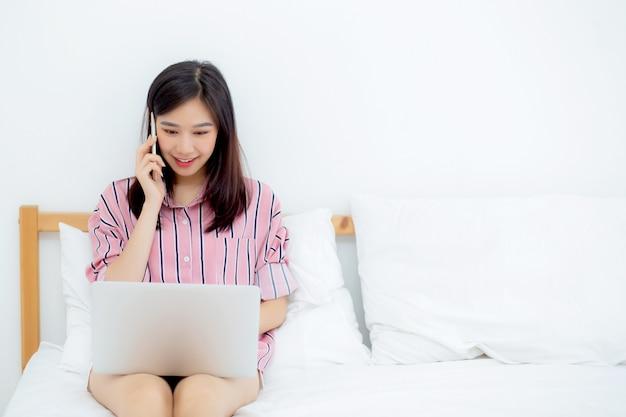 Schöne asiatische frau, die auf bett unter verwendung der laptop-computers sitzt