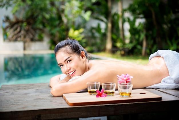 Schöne asiatische frau, die auf massagetabelle liegt und sich entspannt