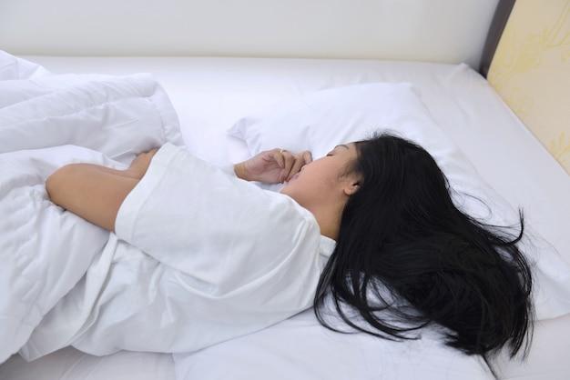 Schöne asiatische frau, die bequem mit schläft