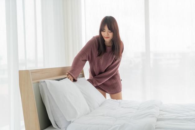 Schöne asiatische frau, die bett im zimmer mit weißem sauberem laken macht