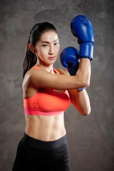 Schöne asiatische frau, die boxtraining am gesundheitsclub tut