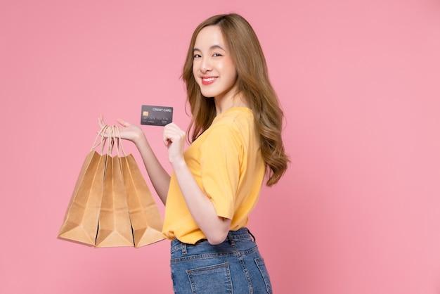 Schöne asiatische frau, die braune leere handwerkspapiereinkaufstaschen hält und kreditkarte auf rosa hintergrund zeigt.