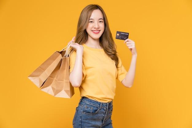 Schöne asiatische frau, die braune leere kraftpapiereinkaufstaschen hält und kreditkarte auf gelbem hintergrund zeigt.
