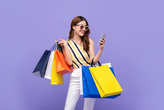 Schöne asiatische frau, die bunte taschen trägt, die online mit handy einkaufen