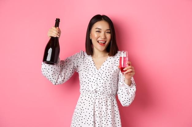 Schöne asiatische frau, die champagner trinkt und lächelt