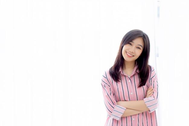 Schöne asiatische frau, die das fenster und lächeln während aufstehen steht