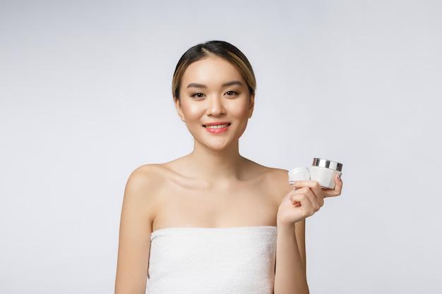 Schöne asiatische frau, die das produkt lokalisiert auf weißem hintergrund darstellt.