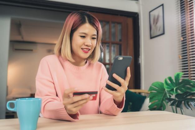 Schöne asiatische frau, die den smartphone verwendet, der online durch kreditkarte kauft