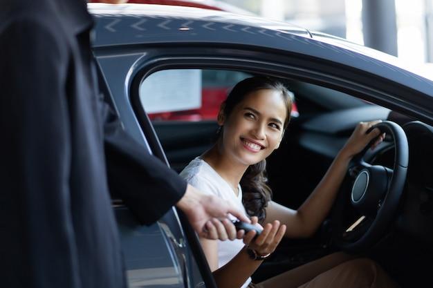 Schöne asiatische frau, die ein auto am ausstellungsraum kauft