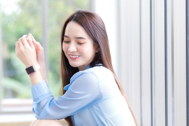 Schöne asiatische frau, die ein blaues hemd und eine intelligente uhr trägt, lächelt glücklich und sitzt dicht vor den augen