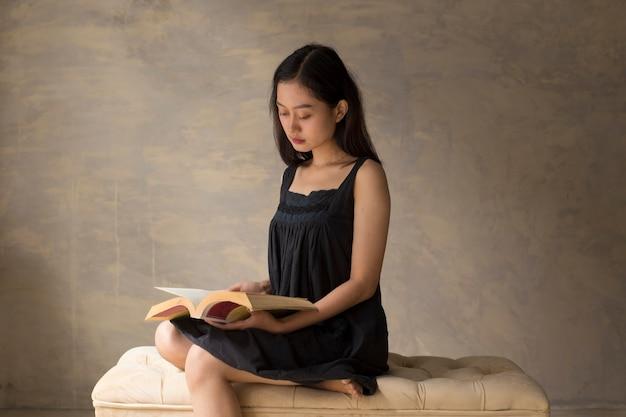 Schöne asiatische frau, die ein buch liest