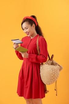 Schöne asiatische frau, die ein rotes kleid trägt und über einem orange hintergrund steht