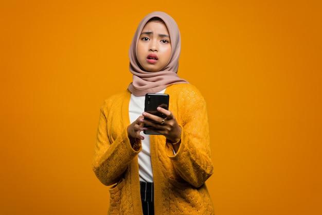 Schöne asiatische frau, die ein smartphone mit einem schockierten gesicht verwendet
