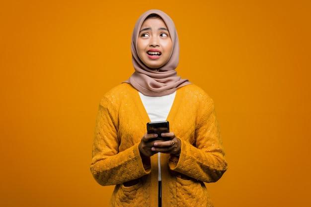 Schöne asiatische frau, die ein smartphone mit einem verwirrten gesicht verwendet