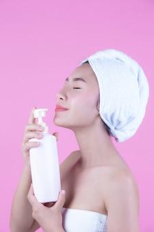 Schöne asiatische frau, die eine flasche des produktes auf einem rosafarbenen hintergrund anhält.
