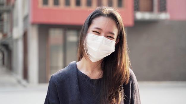 Schöne asiatische frau, die eine medizinische schutzmaske trägt und auf der straße steht. sichere und glückliche frau, die soziale distanzierung praktiziert, quarantäne. gesundheitsversorgung und medizinisches konzept. porträt hautnah. 4k