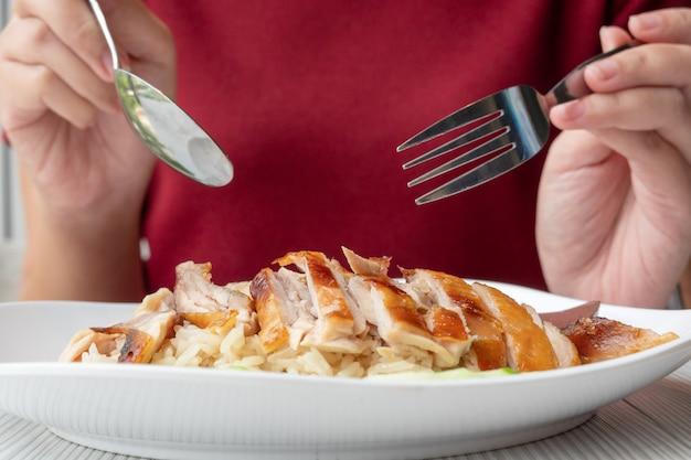 Schöne asiatische frau, die einen löffel hält, um auf der platte zu essen, die gegrilltes huhn ist
