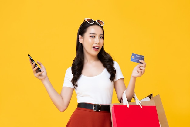 Schöne asiatische frau, die einkaufstaschen trägt, die kreditkarte in der hand zeigen