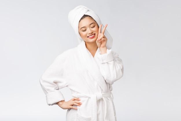 Schöne asiatische frau, die friedenszeichen oder zwei finger mit glücklichem gefühl zeigt, über isoliert