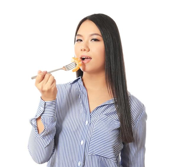 Schöne asiatische frau, die garnelen auf weißem hintergrund isst