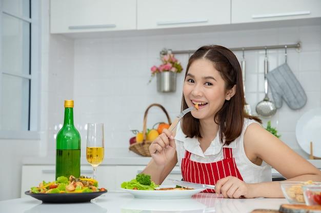 Schöne asiatische frau, die gegrilltes schweinesteak von der gabel mit grünem eichengemüse und salat in der schale hält. ideen für gesundes kochen und gewichtsverlust.