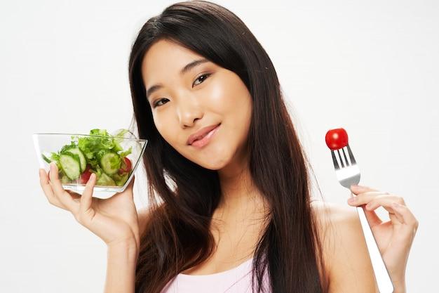 Schöne asiatische frau, die gemüse isst