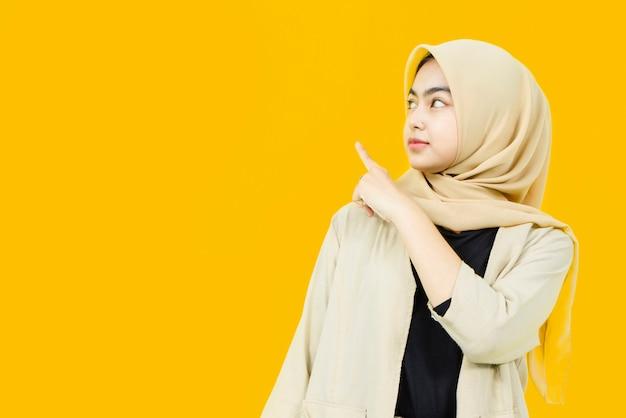 Schöne asiatische frau, die hand auf leeren raum auf gelber wand zeigt