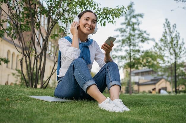 Schöne asiatische frau, die handy verwendet, musik im freien hörend, auf gras im park sitzend
