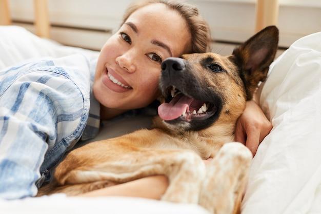 Schöne asiatische frau, die hund umarmt