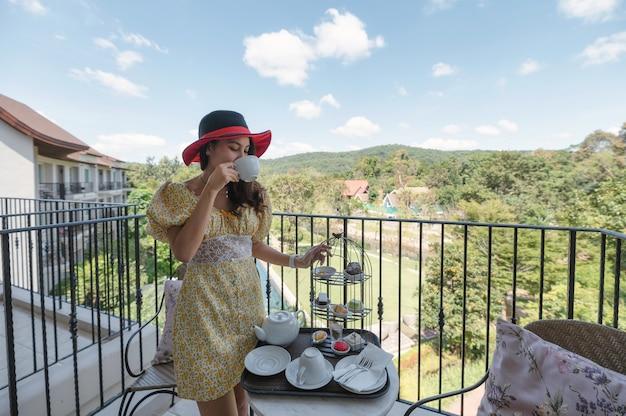 Schöne asiatische frau, die hut trägt, der nachmittagstee und nachtisch am balkon im englischen garten genießt