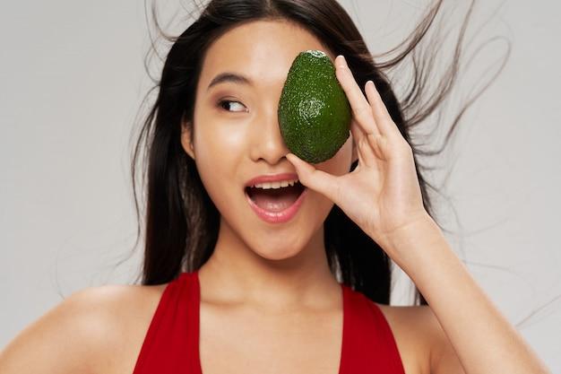 Schöne asiatische frau, die ihr auge mit einer avocado bedeckt