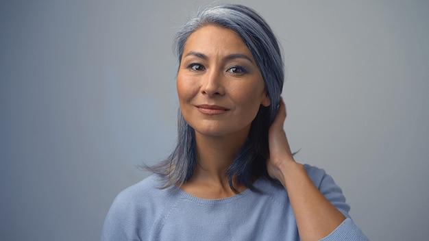 Schöne asiatische frau, die ihr graues haar aufräumt