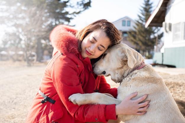 Schöne asiatische frau, die ihren schoßhund labrador-apportierhund umarmt