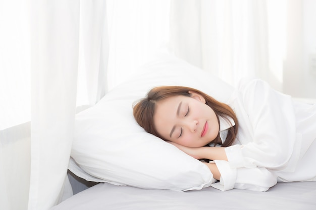 Schöne asiatische frau, die im bett liegend schläft