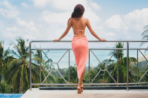 Schöne asiatische frau, die im rosa bikini-badeanzug und im pareo auf der terrasse auf tropischer villa aufwirft, die glücklich im urlaub in thailnad lächelt, sexy körpersommerart, blick von hinten, blick auf landschaft