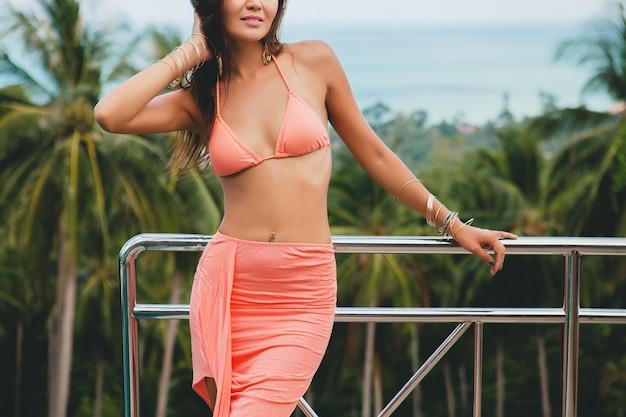 Schöne asiatische frau, die im rosa bikini-badeanzug und im pareo auf terrasse auf tropischer villa aufwirft, die glücklich im urlaub in thailnad, sexy körpersommerart lächelt