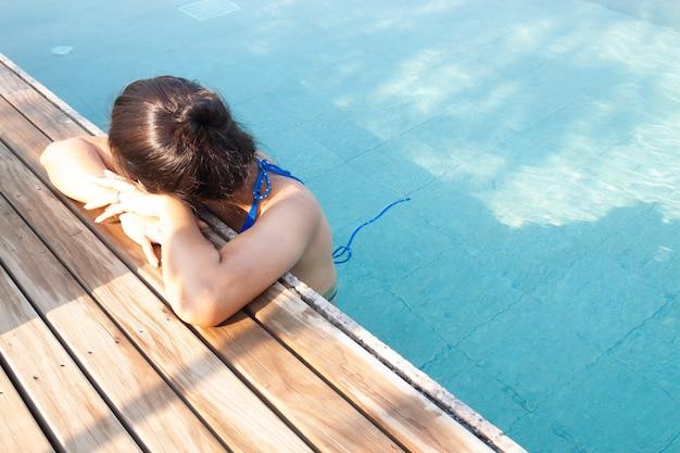 Schöne asiatische frau, die im swimmingpool sich entspannt.