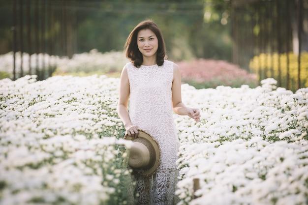 Schöne asiatische frau, die im tropischen blumengarten mit glücksart mit warmem sonnenlicht vom hintergrund geht und lächelt.