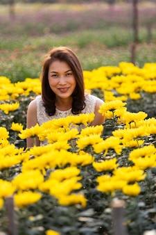 Schöne asiatische frau, die im tropischen blumengarten mit glücksart mit warmem sonnenlicht vom hintergrund steht und lächelt.