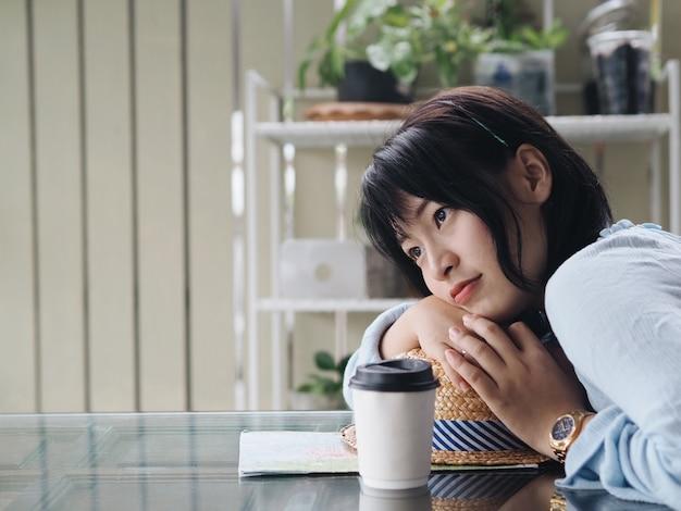 Schöne asiatische frau, die in der kaffeestube sich entspannt.