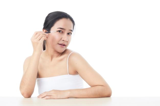 Schöne asiatische frau, die in die kamera schaut und mit einem kleinen kosmetikpinsel in ihr eine hand hob, um ihren augenbrauenkopfschuss mit nackten schultern auf weißer oberfläche zu konturieren