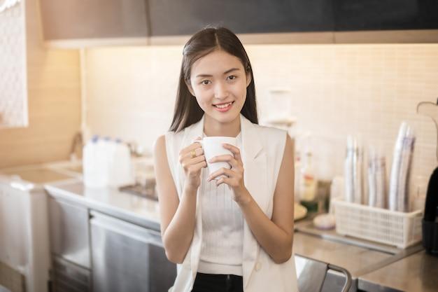 Schöne asiatische frau, die kaffee in einem café-barista riecht und vorbereitet