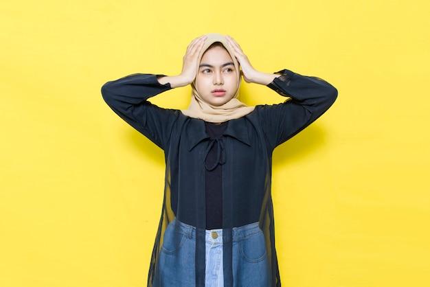 Schöne asiatische frau, die kopfschmerzen in den schwarzen kleidern hat