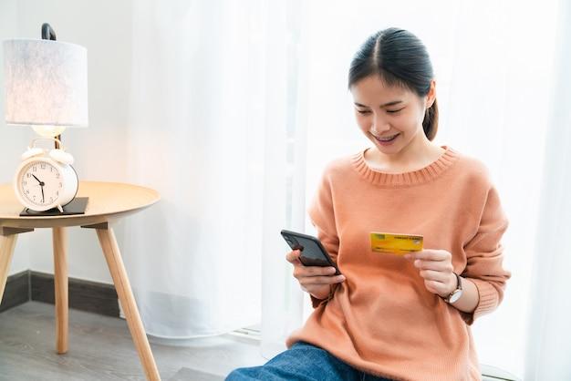 Schöne asiatische frau, die kreditkarte und smartphone mit online-shopping hält