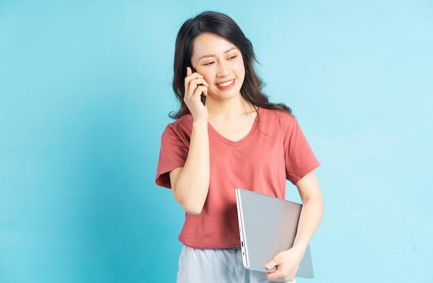 Schöne asiatische frau, die laptop in der hand hält, während sie einen anruf tätigt