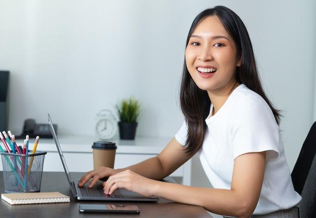 Schöne asiatische frau, die laptop verwendet und am tisch im innenministerium sitzt.